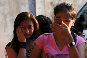 Women weep as they look for missing relatives that were trapped in a fire at a factory in Valenzuela, Metro Manila in the Philippines May 13, 2015. REUTERS/Ezra Acayan